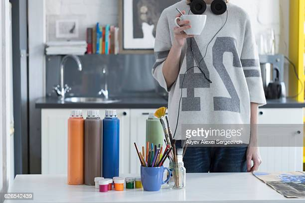 Female artist drinking coffee at kitchen table
