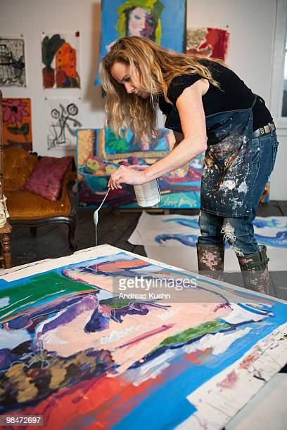 Female artist dripping paint onto her artwork.