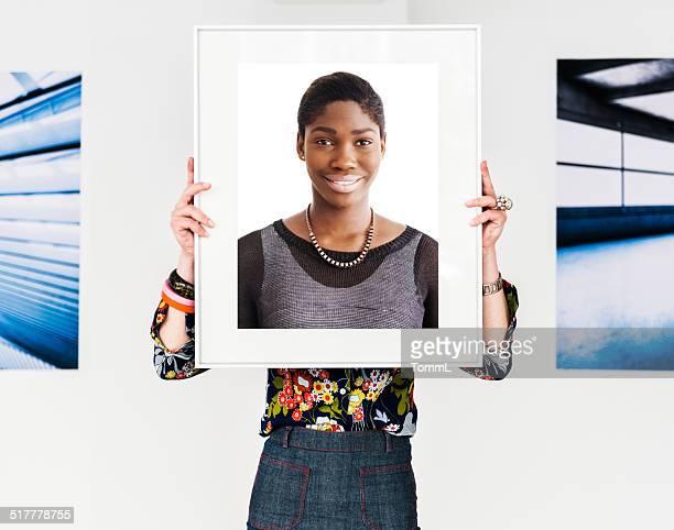 Weibliche Künstler halten Bilderrahmen auf Ihr Gesicht