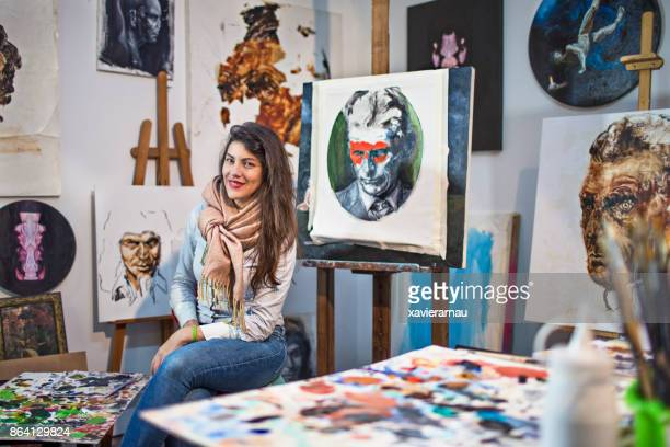 Female artist in her studio surrounded by her painting art