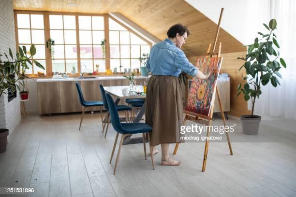 アトリエのキャンバスに指で痛む女性アーティスト - ワイドショット ストックフォトと画像