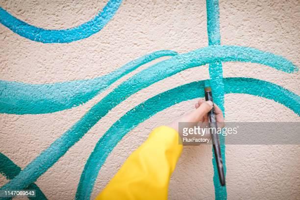 artista donna che dipinge una bicicletta sul muro - murale foto e immagini stock