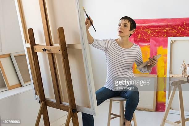 female artist painting in her studio - fine art painting stock pictures, royalty-free photos & images