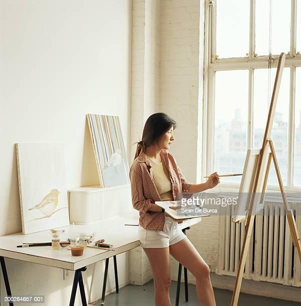 female artist painting in studio - staffelei stock-fotos und bilder
