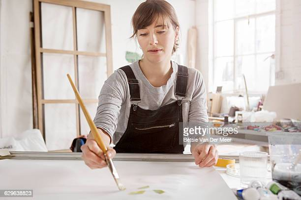 female artist paints in studio. - painting stock pictures, royalty-free photos & images