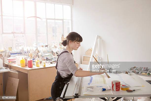 Female artist paints in studio.