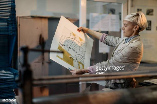 female artist proudly showing her etching on wet paper - etching stock pictures, royalty-free photos & images