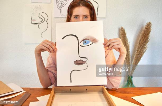female artist showing charcoal drawing against wall at home - fotografia arte e artesanato - fotografias e filmes do acervo