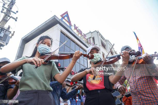 Female artists play musical instruments during the military coup protest in Mandalay. A massive crowd took to the streets of Mandalay to protest...