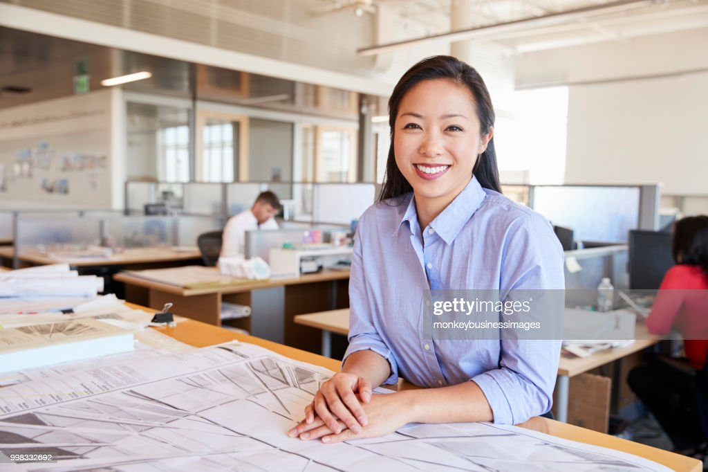 Female Asian architect smiling to camera in open plan office : Stock Photo