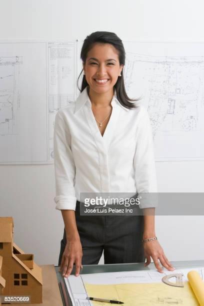 Female Asian architect standing at desk