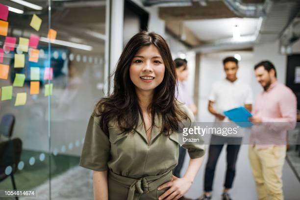 mujer empresaria asiática en oficina con su equipo multiétnico - equidad de genero fotografías e imágenes de stock