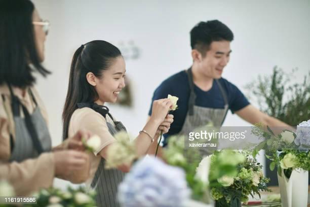 彼女の笑顔の同僚と話す女性アジアの花屋 - フラワーアレンジメント ストックフォトと画像
