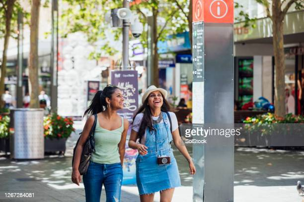 female asian friends walking down city street - perth australia stock pictures, royalty-free photos & images