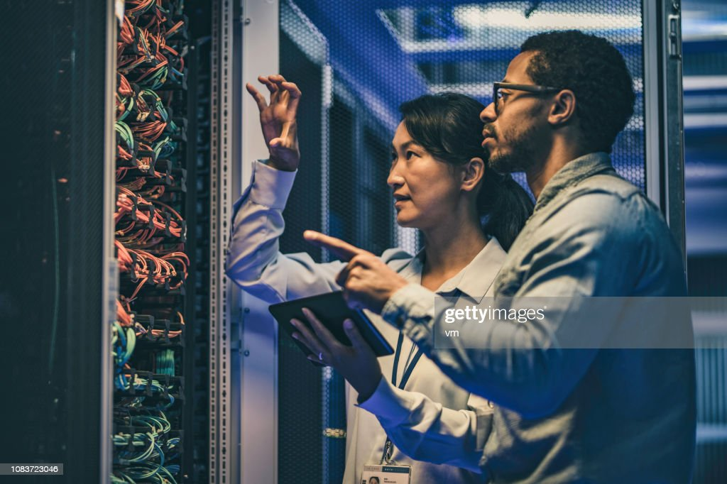 Female Asian IT technician explaining network connection to a novice engineer : Stock Photo
