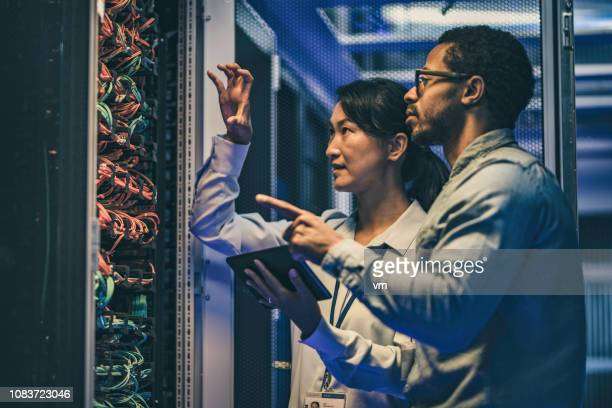 female asian it technician explaining network connection to a novice engineer - data center stock pictures, royalty-free photos & images