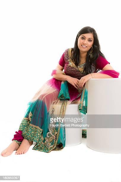 Female Asian model sitting in colourful dress