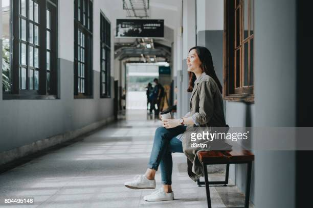 Female Asian student enjoying coffee and resting on bench in college