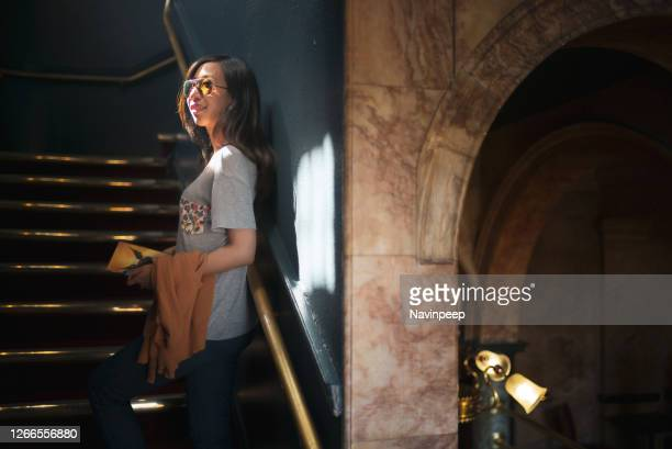 female asian tourist standing inside an old london building - vintage raincoat stock pictures, royalty-free photos & images