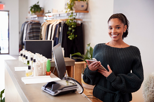 Female assistant smiling from the counter in clothing store 901866542