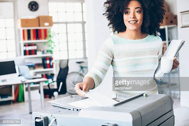 Ayudante femenina con fotocopiadora en lugar de trabajo