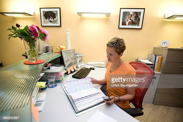 Female assistent in the reception area of a dental practice on May 14 2014 in Cologne Germany