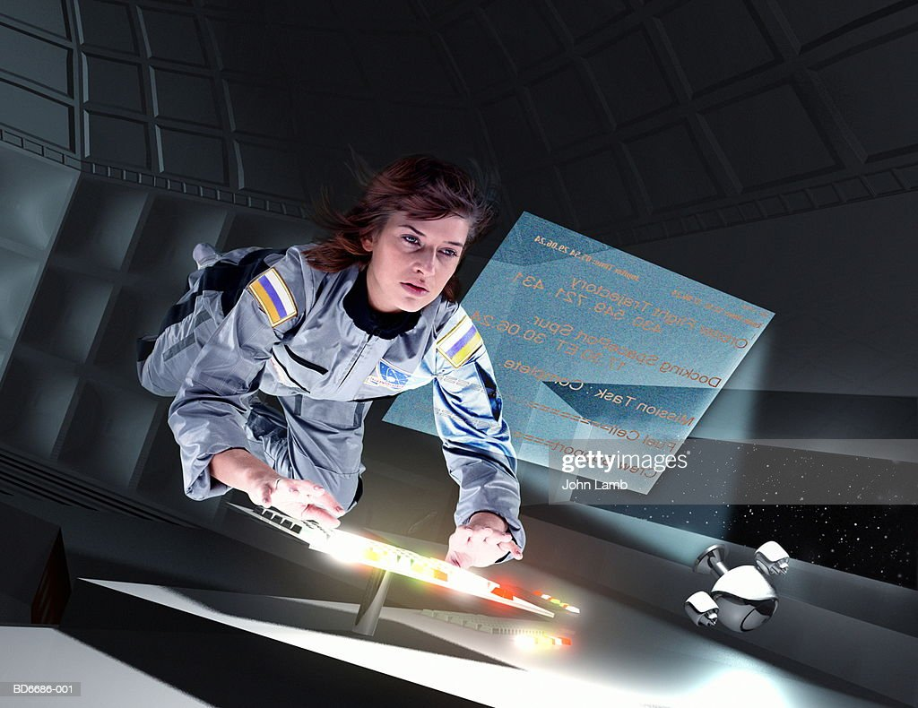 Female astronaut floating in space station (Digital Composite) : Stock Photo