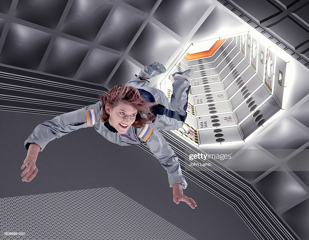 Female astronaut floating in space station (Digital Composite) : Stockfoto