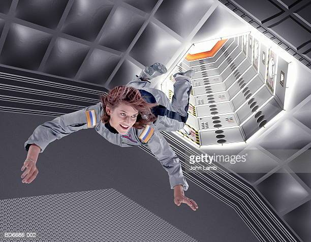 female astronaut floating in space station (digital composite) - space station stock pictures, royalty-free photos & images