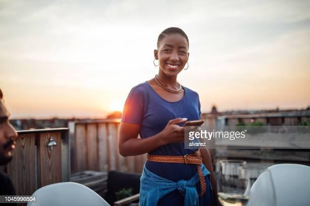 Frau auf Party auf dem Dach mit Telefon