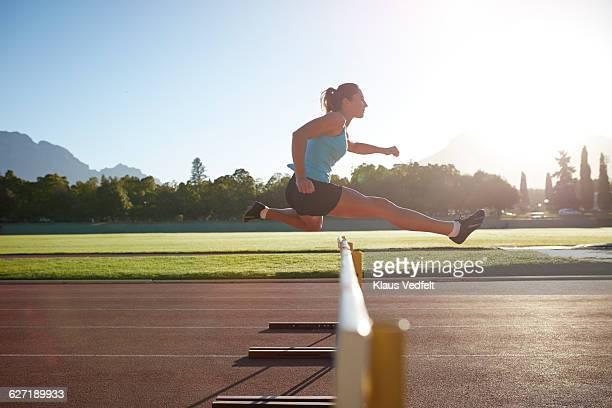 Female athelete jumping over hurdle at sunrise