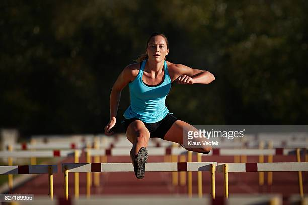 female athelete jumping over hurdle at sunrise - hurdling track event stock pictures, royalty-free photos & images