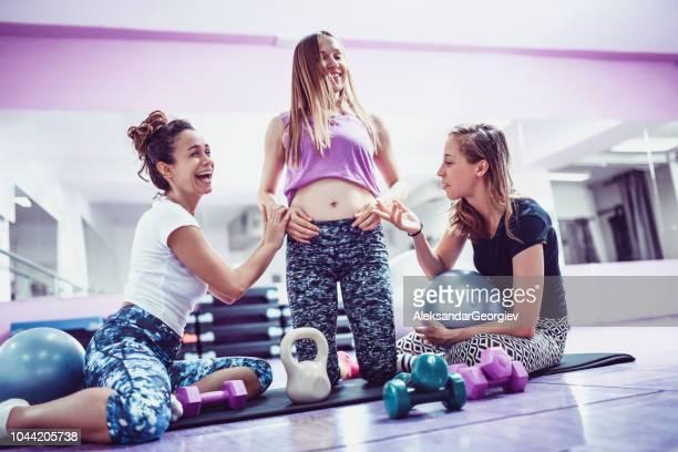 athlète féminine annonçant la grossesse à ses amis après la séance d'entraînement - annonce grossesse photos et images de collection