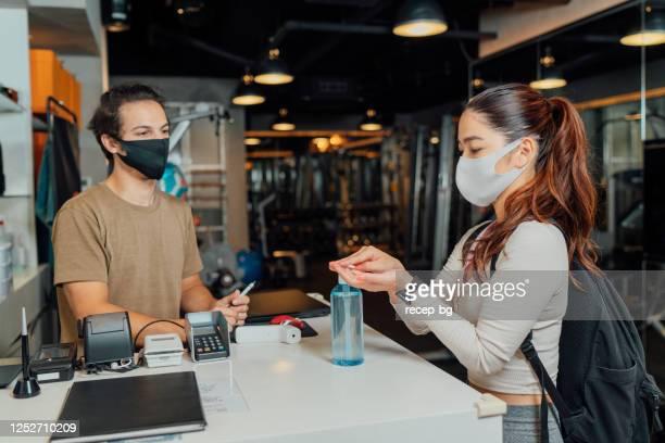 ジムの入り口で手指消毒剤ジェルを塗布する女性アスリート - 消毒薬 ストックフォトと画像