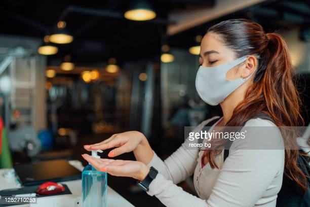 female athlete applying hand sanitizer gel at entrance of gym - antiseptic stock pictures, royalty-free photos & images