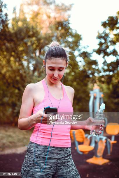 female athlete changing song on smartphone while hydrating after workout - colors soundtrack stock pictures, royalty-free photos & images