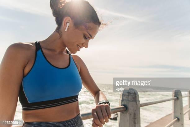 vrouwelijke atleet controle van haar puls op slimme horloge - sportbeha stockfoto's en -beelden