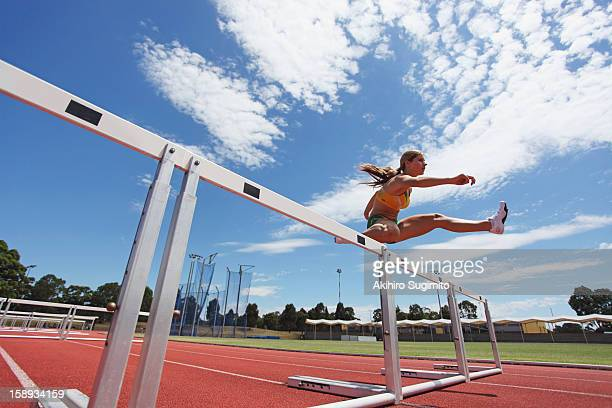 Female Athlete Clearing Hurdles