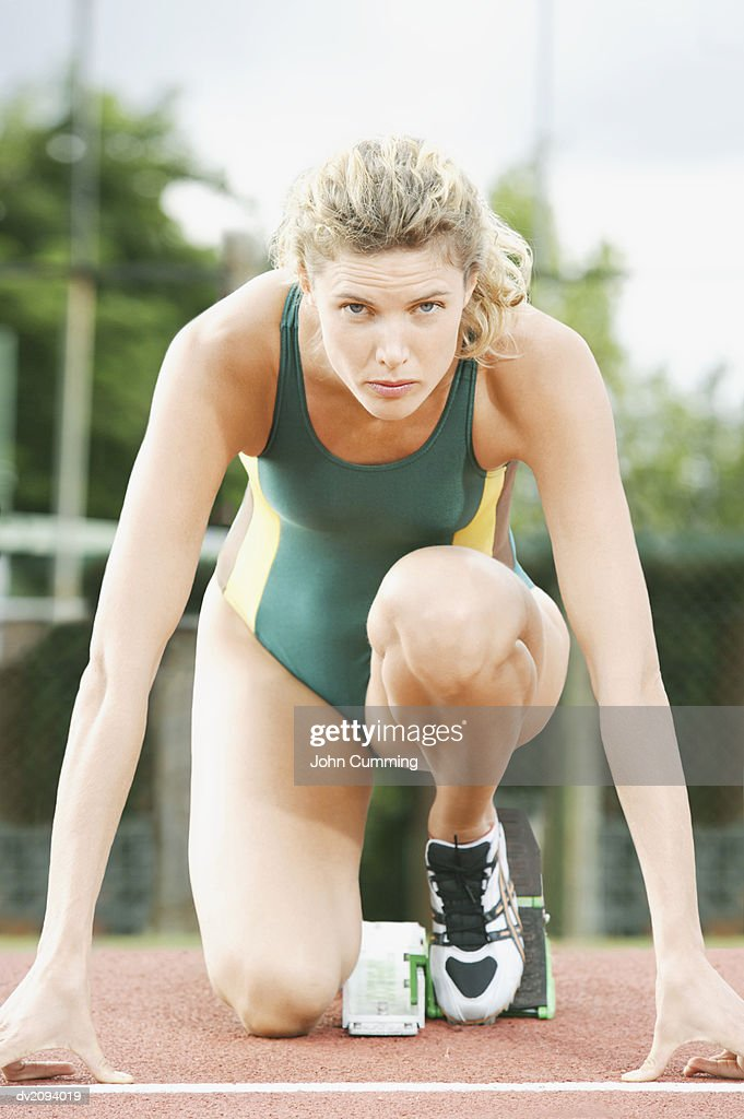 Female Athlete Crouching on the Starting Blocks of a Running Track : Stock Photo