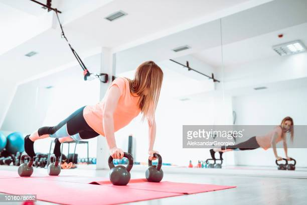 Female Athlete Doing Balance Plank Exercises With Kettlebell