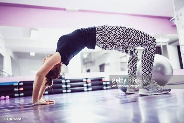 sportlerin, die gymnastische brücke trainieren im fitness-studio - junge frau strumpfhose stock-fotos und bilder