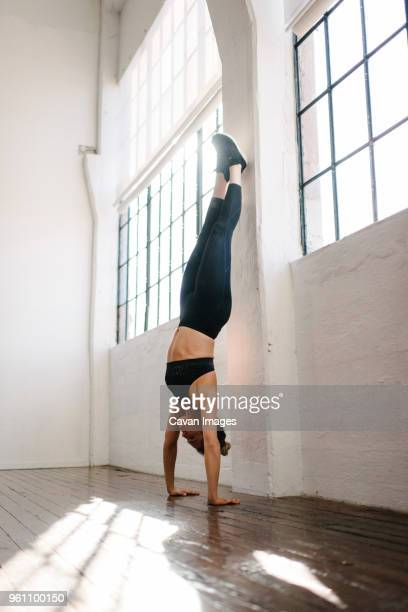 female athlete doing handstand in gym - handstand stock pictures, royalty-free photos & images