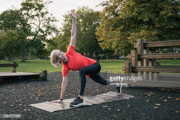 female athlete doing lunge stretch with thoracic rotation - clapham common stock pictures, royalty-free photos & images