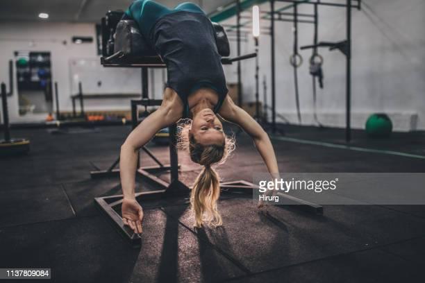 athlète femelle faisant des pull-ups sur le banc romain - blonde forte poitrine photos et images de collection