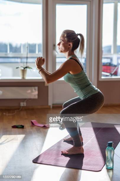 female athlete doing squats. - slim stock pictures, royalty-free photos & images