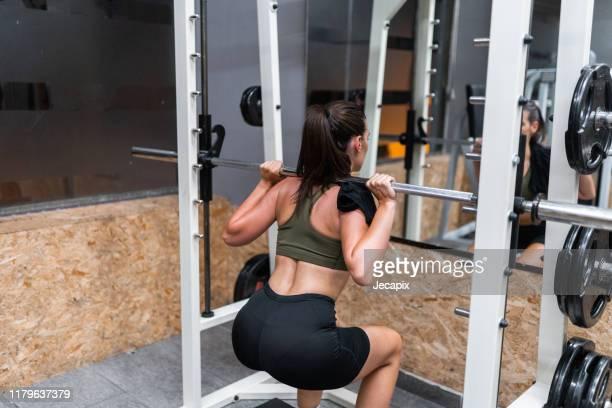 female athlete doing squats with weights in gym - bunda imagens e fotografias de stock