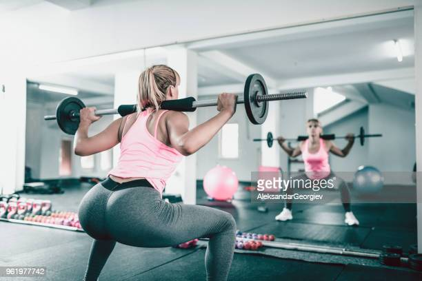 female athlete doing squats with weights in gym - barbell stock pictures, royalty-free photos & images