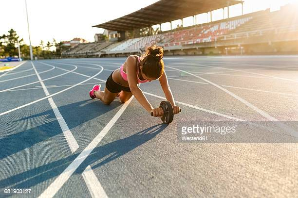 female athlete doing strength training with a roller - track and field stadium stock pictures, royalty-free photos & images