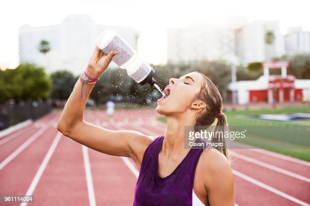 Female athlete drinking water on race tracks