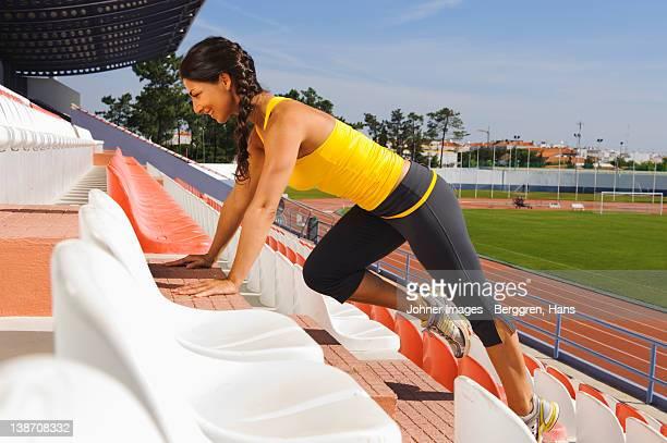 Female athlete exercising at stadium steps